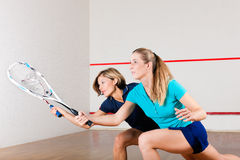 Squash sport - women playing on gym court. Two women playing squash as racket sport in gym, it might be a competition Royalty Free Stock Images