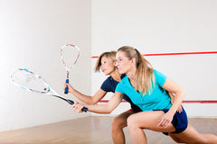 Squash sport - women playing on gym court. Two women playing squash as racket sport in gym, it might be a competition Stock Photo