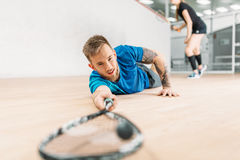 Squash training, player with racket lies on floor. Squash training, male player with racket lies on the floor. Active sport workout. Game with ball and racquet Royalty Free Stock Photo