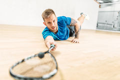 Squash training, player with racket lies on floor. Squash training, male player with racket lies on the floor. Active sport workout. Game with ball and racquet Stock Image