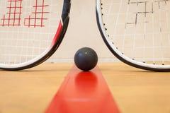 Squashball zwischen zwei Kürbisschlägern Lizenzfreie Stockfotografie