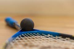squashracket och bollar på domstolen royaltyfria bilder
