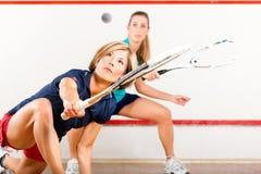 Squashsport - kvinnor som leker på idrottshalldomstolen Arkivbilder