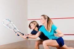 Squashsport - kvinnor som spelar på idrottshalldomstolen Royaltyfria Bilder