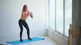 squat Όμορφη νέα γυναίκα που κάνει τη στάση οκλαδόν στο στούντιο ικανότητας απόθεμα βίντεο