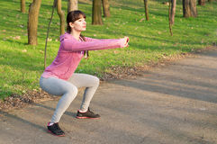 Squat exercises. Strong sporty woman doing squat exercises outdoors on fresh air in the park on a sunny spring day. Copy space Royalty Free Stock Photos