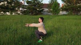 squat Hombre que hace posición en cuclillas al aire libre en el aire abierto Él que hace ejercicios almacen de metraje de vídeo
