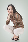Squat pose by sexy Asian beauty Stock Image
