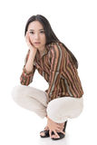 Squat pose by sexy Asian beauty Royalty Free Stock Photography