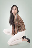 Squat pose by sexy Asian beauty Royalty Free Stock Image