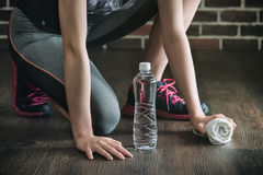 Squat on wooden floor take rest drinking water, fitness exercise Royalty Free Stock Images