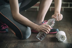 Squat on wooden floor take rest drinking water, fitness exercise Royalty Free Stock Image