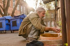 Squating old tramp cleaning face under water. Street hygiene, homeless man washing face Stock Photo