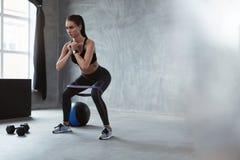 squats Αθλήτρια στα ενδύματα μόδας που κάθεται οκλαδόν με τη ζώνη στοκ εικόνα
