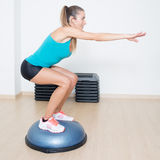 Squats on balance trainer Stock Images