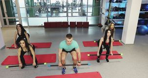 Squats with body bars. Fitness instructor is working with women in fitness gym. Steady cam shot stock video footage