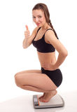 Squats on scale young woman thumb up Royalty Free Stock Images