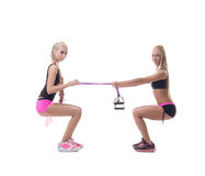 Squats. Two sexy blondes exercising with expander Stock Image