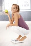 Squatter girl on scale holding apple Royalty Free Stock Image