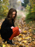 Squatting beauty girl in fall outdoor. Squatting pretty young girl in fall forest Stock Photo