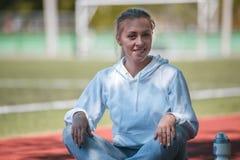 squatting jonge beauty girl do exercises bij het stadion Royalty-vrije Stock Foto's