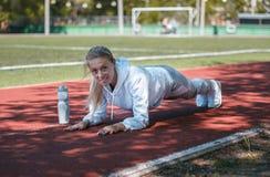 squatting jonge beauty girl do exercises bij het stadion Stock Foto