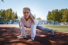 squatting jonge beauty girl do exercises bij het stadion Stock Afbeelding