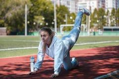 squatting jonge beauty girl do exercises bij het stadion Stock Afbeeldingen