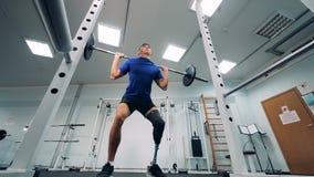 Squatting med en stång av en man med ett prosthetic ben arkivfilmer