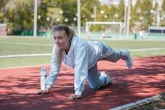 squatting a menina nova da beleza faz exercícios no estádio Fotografia de Stock