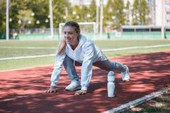 squatting a menina nova da beleza faz exercícios no estádio Fotografia de Stock Royalty Free