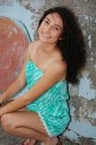 Squatting modelo adolescente contra um muro de cimento Imagens de Stock Royalty Free