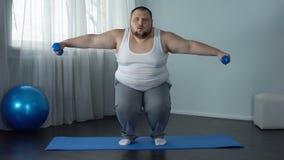 Squatting och lyftande hantlar för överviktig man på mattt fullt kropputbildningshem lager videofilmer