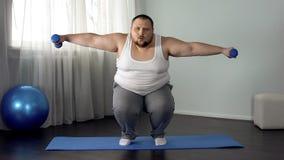 Squatting och lyftande hantlar för överviktig man på mattt fullt kropputbildningshem arkivbilder