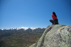 Squatting på överkanten av dalen Arkivfoto