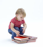 Squatting small look at book young girl Stock Photography