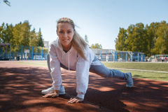 Squatting.young beauty girl do exercises at the stadium Stock Image