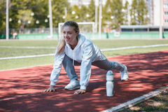 Squatting.young beauty girl do exercises at the stadium Royalty Free Stock Photography