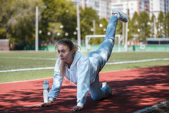 Squatting.young beauty girl do exercises at the stadium Stock Images