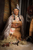 Squaw with peace pipe. Weathered mature tribal female storyteller talking about heroic times Royalty Free Stock Image