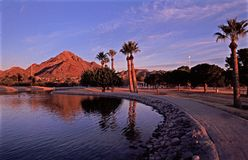 Squaw Peak at Sunset in Phoenix. View of Squaw Peak from Phoenix Park at sunset. Waterfront path lined with palm trees Royalty Free Stock Photography