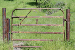 Squeaky Gate. A rusty, squeaky gate, with tall green grass, and an arrow, in the background pointing towards a hiking trail Stock Image