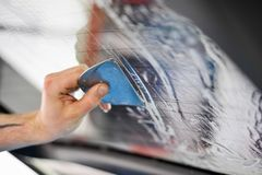 Squeegeeing car window with squeegee stock image