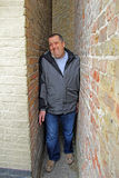 Squeeze gut alley man. Photo of a man stuck between two walls of buildings in an alleyway called squeeze gut alley in whitstable kent Royalty Free Stock Image