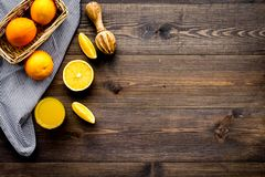 Squeeze juice from oranges. Juicer and slices of oranges on dark wooden background top view copyspace royalty free stock images