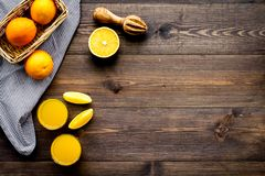 Squeeze juice from oranges. Juicer and slices of oranges on dark wooden background top view copy space royalty free stock photography