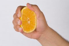 Squeeze the orange. An isolated man hand squeezing an orange slice Stock Photo
