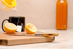 Squeezed lemon poured in a cup of tea Stock Images