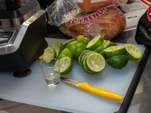 Squeezed lime, shot glass and knife sitting on small cutting board, making margaritas for party stock photos