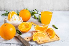 Squeezed orange juice and fresh oranges fruits on white wooden t royalty free stock photography
